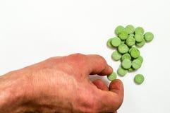 Handen tar de gröna preventivpillerarna Arkivfoto