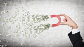 Handen tilldrar pengar arkivbilder