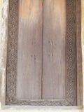 Handen tillverkade arbete av den THAILÄNDSKA konstnären på en röd brun ram för ädelträtempelfönster Arkivfoton