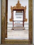 Handen tillverkade arbete av den THAILÄNDSKA konstnären på en röd brun ram för ädelträtempelfönster Royaltyfri Fotografi
