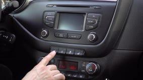 Handen trycker på en upphettad Seat hög knapp på en instrumentbräda i en bil lager videofilmer