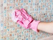 Handen tvättar keramiska tegelplattor på kökväggen Arkivbild