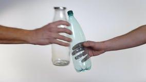Handen vägrar den plast- flaskan för den återvinningsbara glasflaskan, plast- förorening stock video