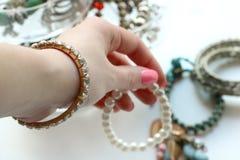 Handen väljer armbandet arkivbild