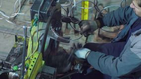 Handen van arbeider en werkende delen van de ketting-makende machine stock videobeelden