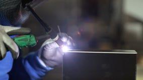 Handen van arbeiderslassen in fabriek stock footage