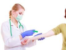 Handen van artsenverpleegster met spuit die injectie geeft aan patiënt Stock Foto's