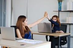 Handen van Aziatische bedrijfsmensen die hoogte vijf na succesvol in bureau geven stock afbeeldingen