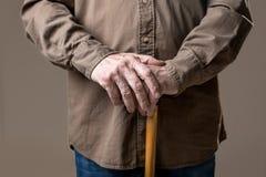 Handen van bejaard mannelijk holdingsriet stock fotografie