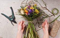 Handen van bloemist die boeket maken bloemen opspringen Stock Fotografie