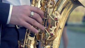 Handen van bruidegomspel op saxofoon Close-uphanden van de mens die gouden altsaxofoon met lichteffect spelen Mensen het spelen stock video