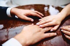 Handen van bruiden op een lijst met dalingen van water tijdens de regen stock fotografie