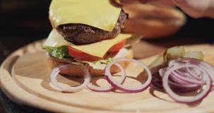 Handen van chef-kok die hamburger maken Langzame Motie stock video