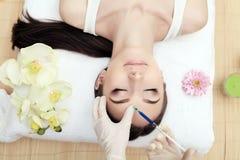 Handen van cosmetologist die injectie in gezicht maken De jonge vrouw krijgt schoonheids gezichtsinjecties in salon Gezichts het  royalty-vrije stock fotografie