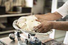 handen van de bakker die het bedrag wegen royalty-vrije stock foto