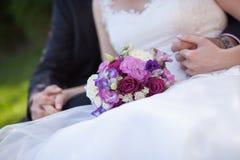 Handen van de bruid en de bruidegom en huwelijksboeket royalty-vrije stock fotografie