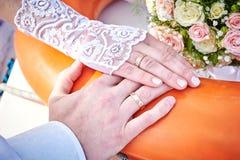 Handen van de bruid en de bruidegom met ringen op een mooi huwelijk Stock Fotografie