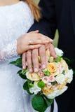 Handen van de bruid en de bruidegom met ringen op een mooi huwelijksboeket Stock Foto's