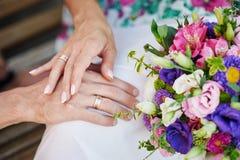Handen van de bruid en de bruidegom met ringen op een mooi huwelijksboeket Royalty-vrije Stock Foto