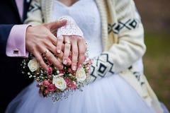 Handen van de bruid en de bruidegom met ringen op een mooi huwelijksboeket Royalty-vrije Stock Foto's
