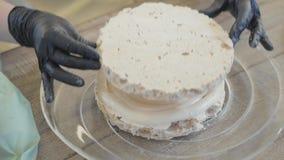 Handen van de chef-kok die in rubberhandschoenen een cake in het close-up van de restaurantkeuken voorbereiden De kok zet de cake stock videobeelden
