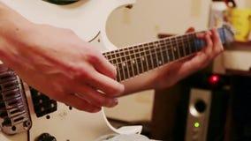 Handen van de jonge mens die moderne witte gitaar spelen stock videobeelden