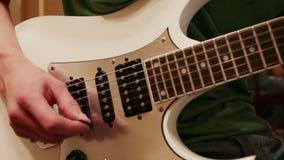 Handen van de jonge mens die witte gitaar spelen stock videobeelden