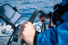 Handen van de kapitein bij de roercontrole van varende boot stock fotografie