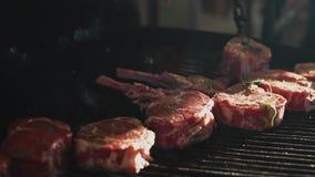 Handen van de mantel die vlees buiten koken Chef die rund ribben op grill zet stock videobeelden