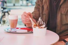Handen van de mens die bevroren yoghurt eten bij koffielijst Royalty-vrije Stock Afbeeldingen