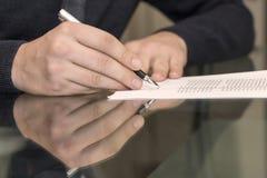 Handen van de mens die formeel document ondertekenen stock afbeeldingen