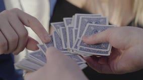 Handen van de mens die houdend een dek van kaarten en handen van vrouw en ander mannetje op kaart richt stock footage