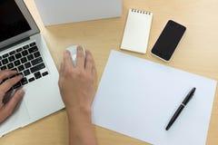 Handen van de mens die laptop met slimme telefoon, tablet, pen, calenda met behulp van Royalty-vrije Stock Afbeelding