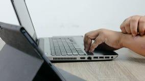 Handen van de mens gebruikend laptop computer en krassend aan de uitbarstingspsoriasis van de wapenhuid stock footage