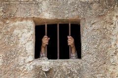 Handen van de mens in gevangenis stock afbeelding