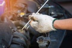 Handen van de Motor van een autoolie van de technicicontrole, selectieve nadruk stock afbeelding