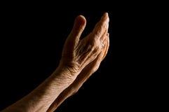 Handen van de oude vrouw op een zwarte achtergrond royalty-vrije stock fotografie