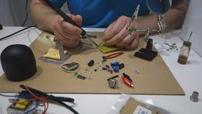 Handen van de reparaties van een mensensoldeersel stock videobeelden