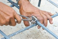 Handen van de scharen van het arbeidersgebruik voor het breien van metaalstaaf Stock Afbeelding