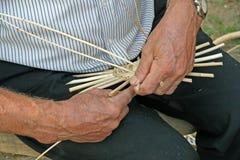 Handen van de vakman terwijl het werken van de rotan om een rijs te maken Stock Foto