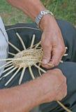 Handen van de vakman terwijl het werken van de rotan om een rijs te maken Royalty-vrije Stock Foto