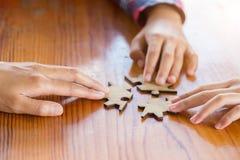 Handen van diverse mensen die puzzel, gezet de Jeugdteam assembleren royalty-vrije stock foto