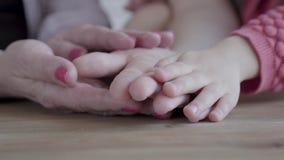 Handen van drie generaties - kleine meisje, moeder en grootmoeder stock video