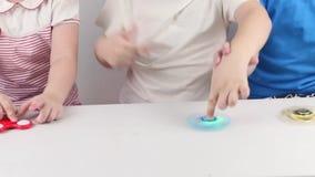 Handen van drie kinderen die met spinners op lijst spelen stock videobeelden