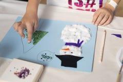 Handen van een 10 éénjarigenmeisje die een Kerstmisambacht doen Stock Foto