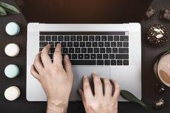 Handen van een amateur die van snoepjes, aan laptop, macarons, koekjes en koffie werken stock foto's
