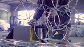 Handen van een arbeider productiemetaal netto in de fabriek stock video