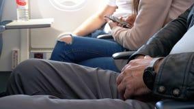 Handen van een bejaarde in de zetel van de vliegtuigen tijdens de vlucht stock video