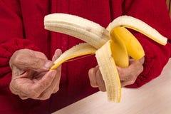 Handen van een bejaarde met een banaan royalty-vrije stock afbeeldingen