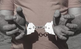 Handen van een brutale mens in handcuffs achter zijn rug op een oranje T-shirt Misdadige straf van opsluiting in gevangenis royalty-vrije stock foto
